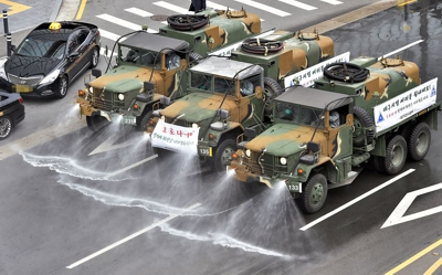 Army vehicles disinfect the road in Daegu about 300 km southeast of Seoul in South Korea