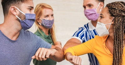 Four peole wearing masks greet each other by touching elbows during the COVID-19 pandemic